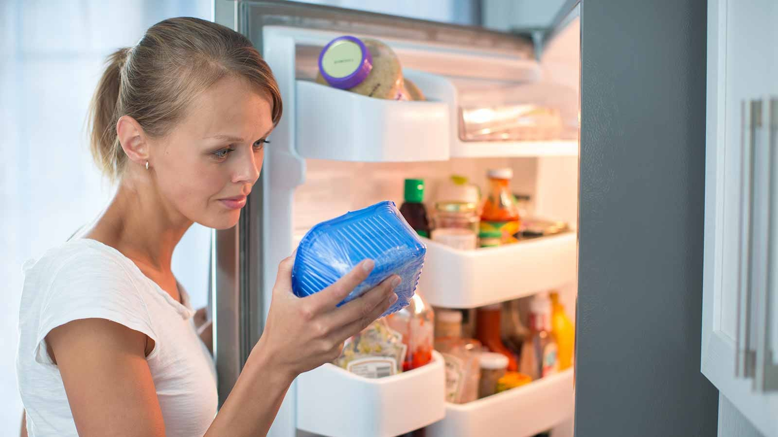 woman scrutinizing the expiration date on a container of food