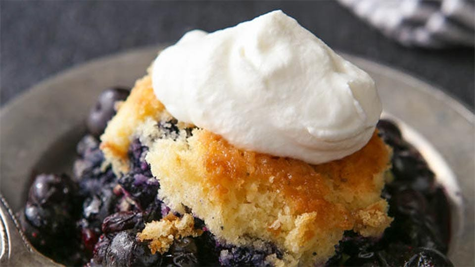 A 4-ingredient fruit cobbler with whipped cream on top on a metal plate.