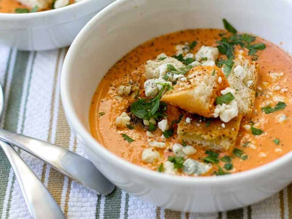 Tomato bisque with bits of bread and basil on top in a bowl.