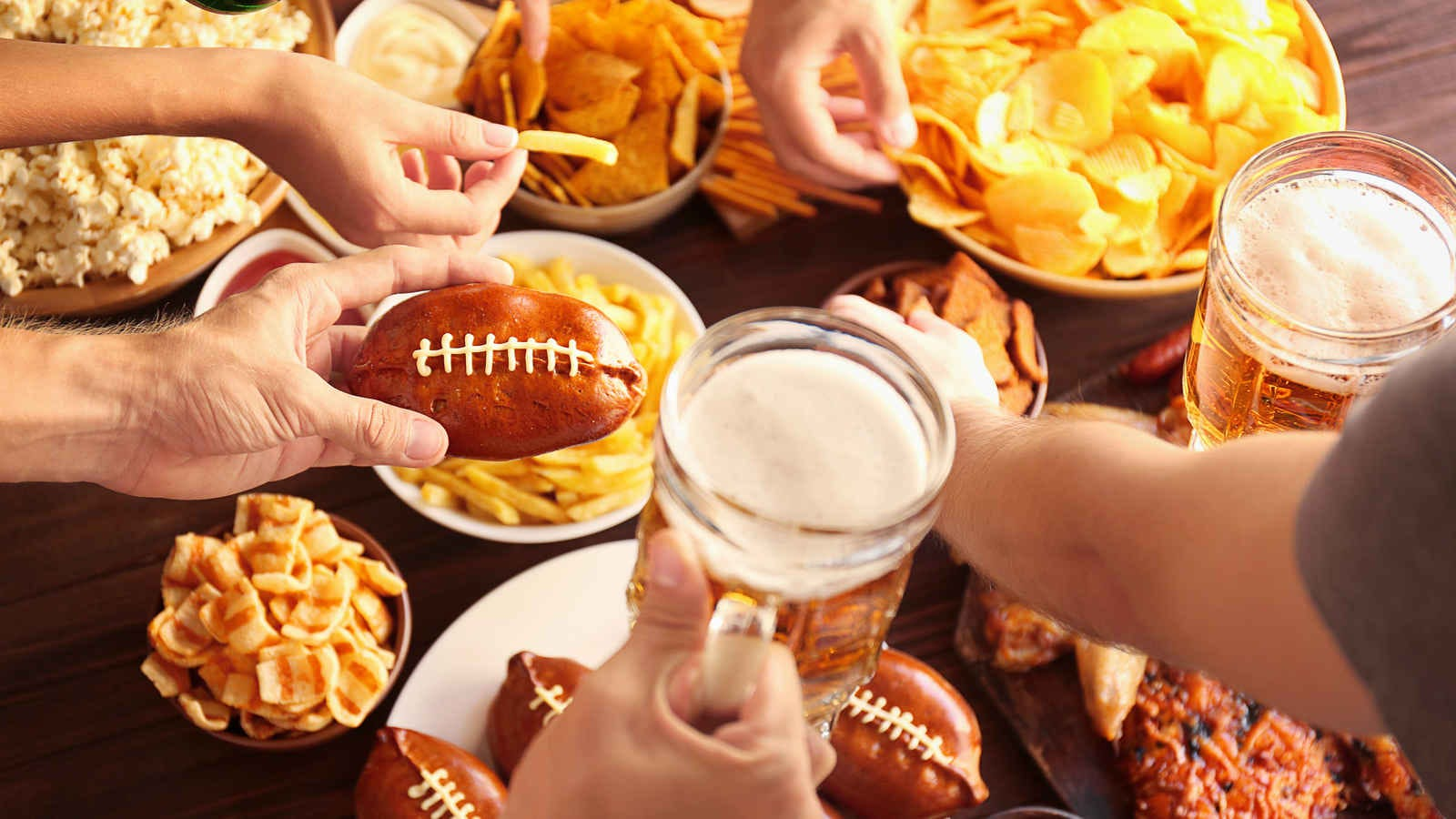 a table loaded with game day appetizers, surrounded by people digging in