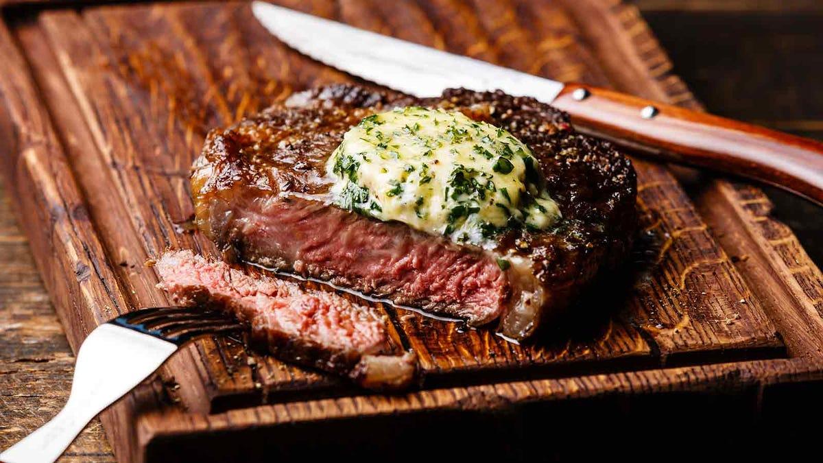 a rich herb compound butter melting atop a juicy steak