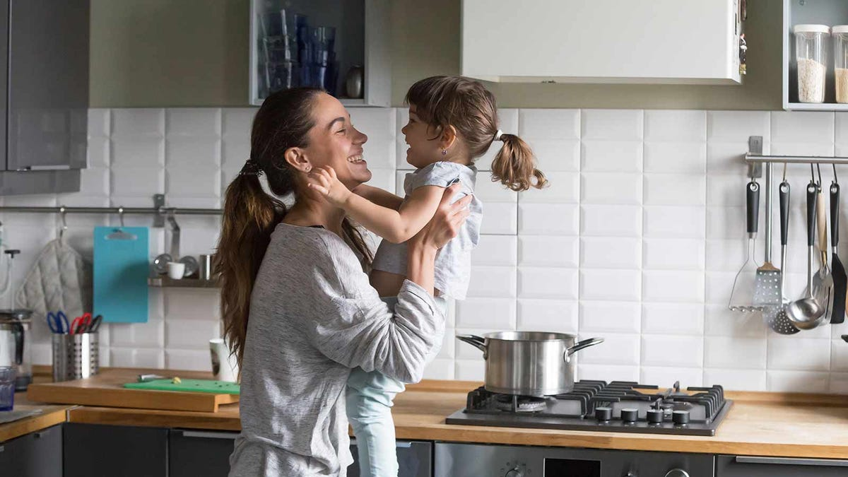 Mother smiling and laughing with her toddler in the kitchen
