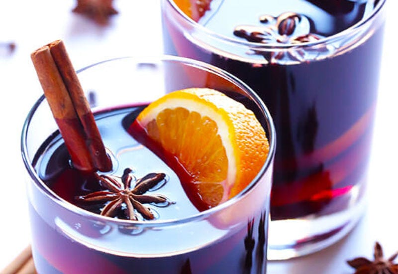 Two glasses of mulled wine, garnished with an orange, a cinnamon stick and star anise.