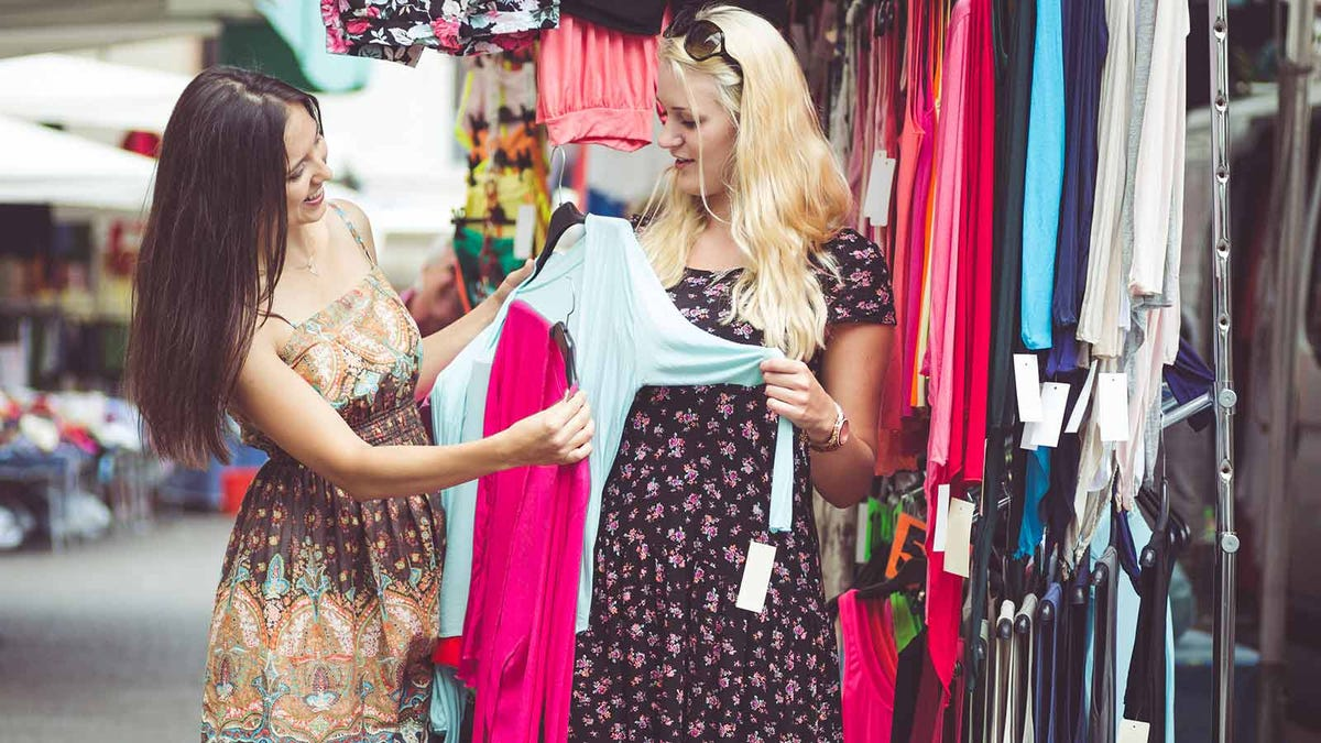 Two women examining blouses at a store.