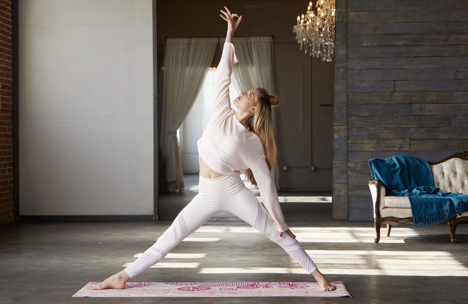 A woman doing a reverse triangle yoga pose in a studio.