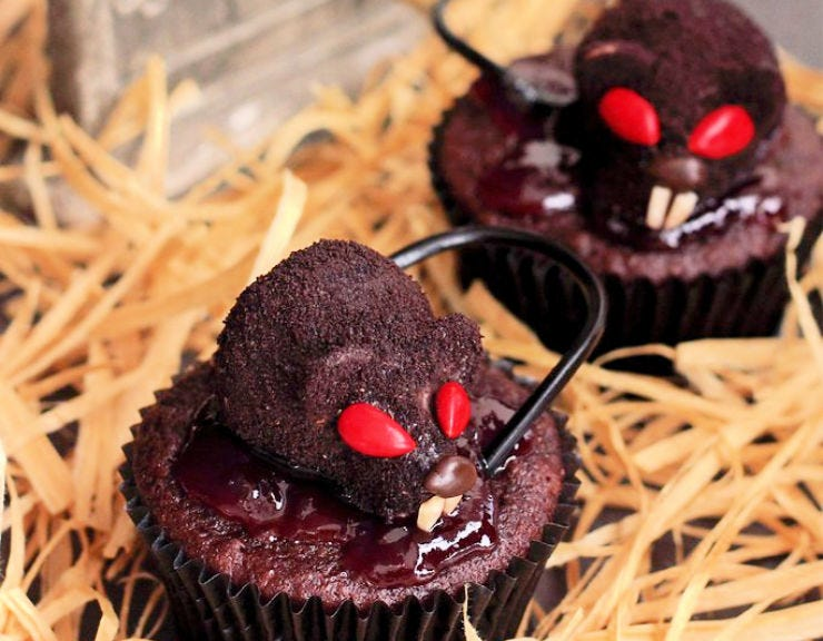 Two cupcakes with chocolate covered strawberries that look like rats.