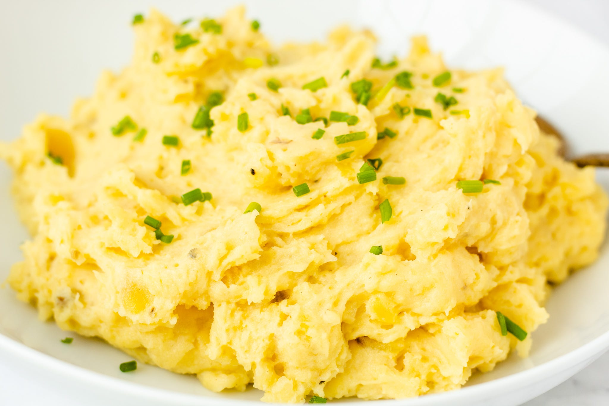 Buttery mashed potatoes with chives sprinkled on top.
