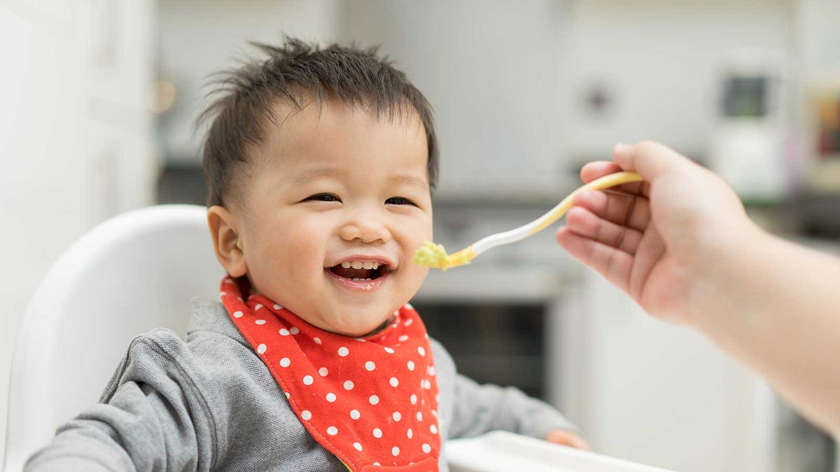 happy baby trying a new kind of baby food