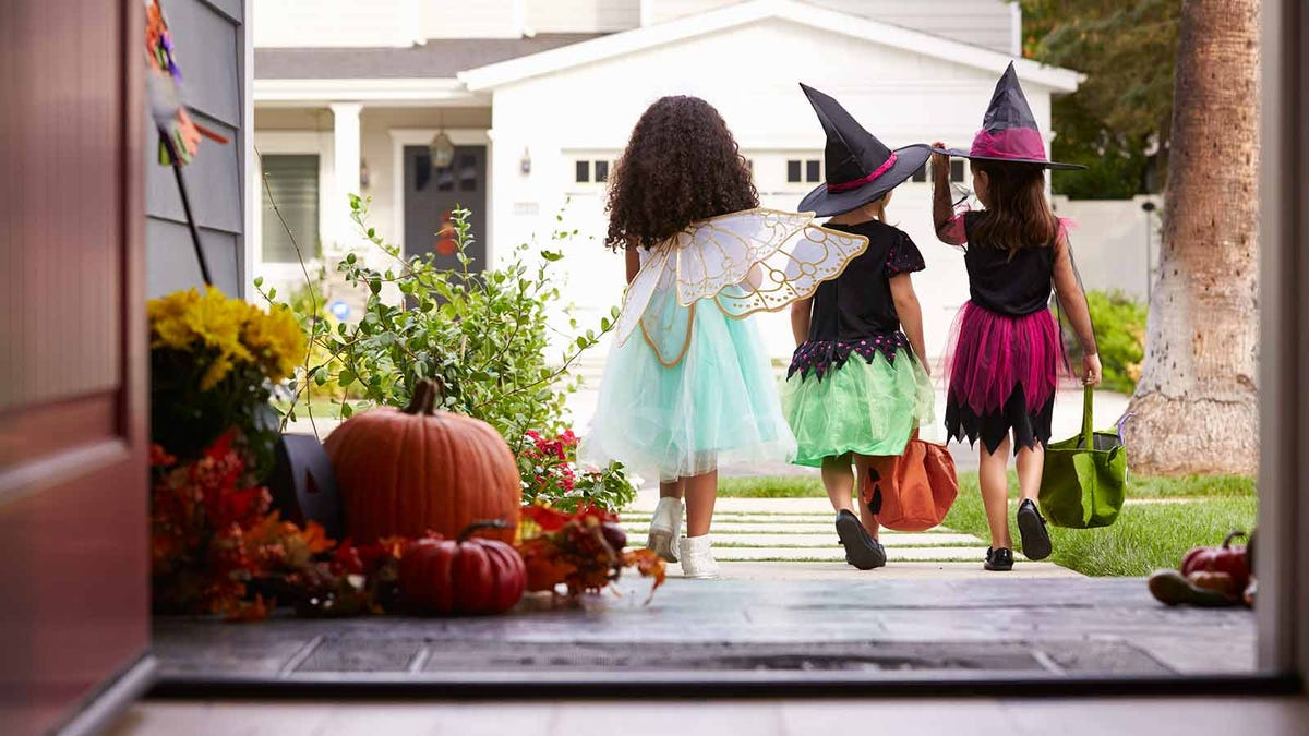 Three little girls in Halloween costumes stepping off a porch with trick or treat bags.