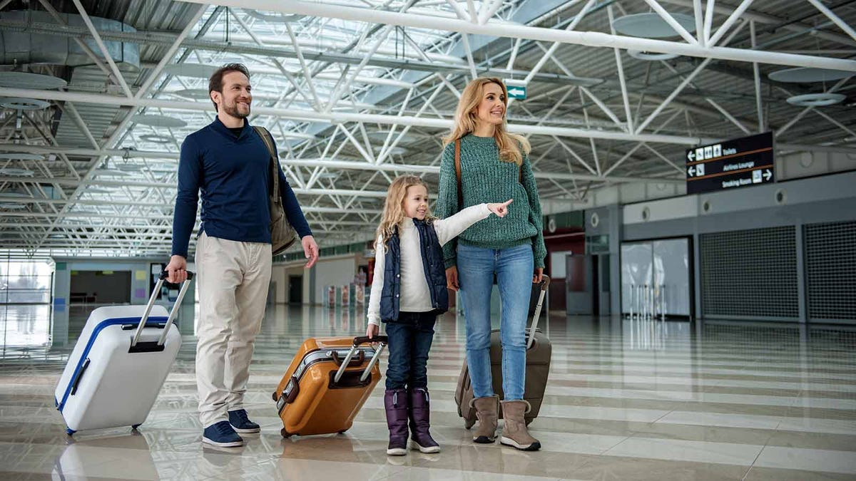 little girl at the airport with her parents pointing out where their gate is