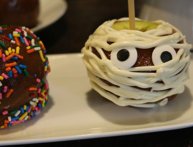 A caramel apple drizzled with white chocolate to resemble a cute mummy.
