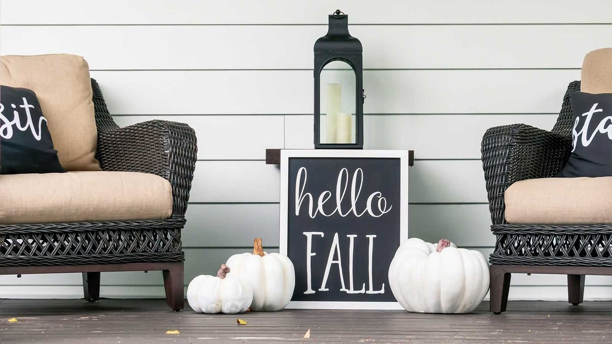a beautifully decorated sitting porch with white pumpkins resting beside outdoor chairs