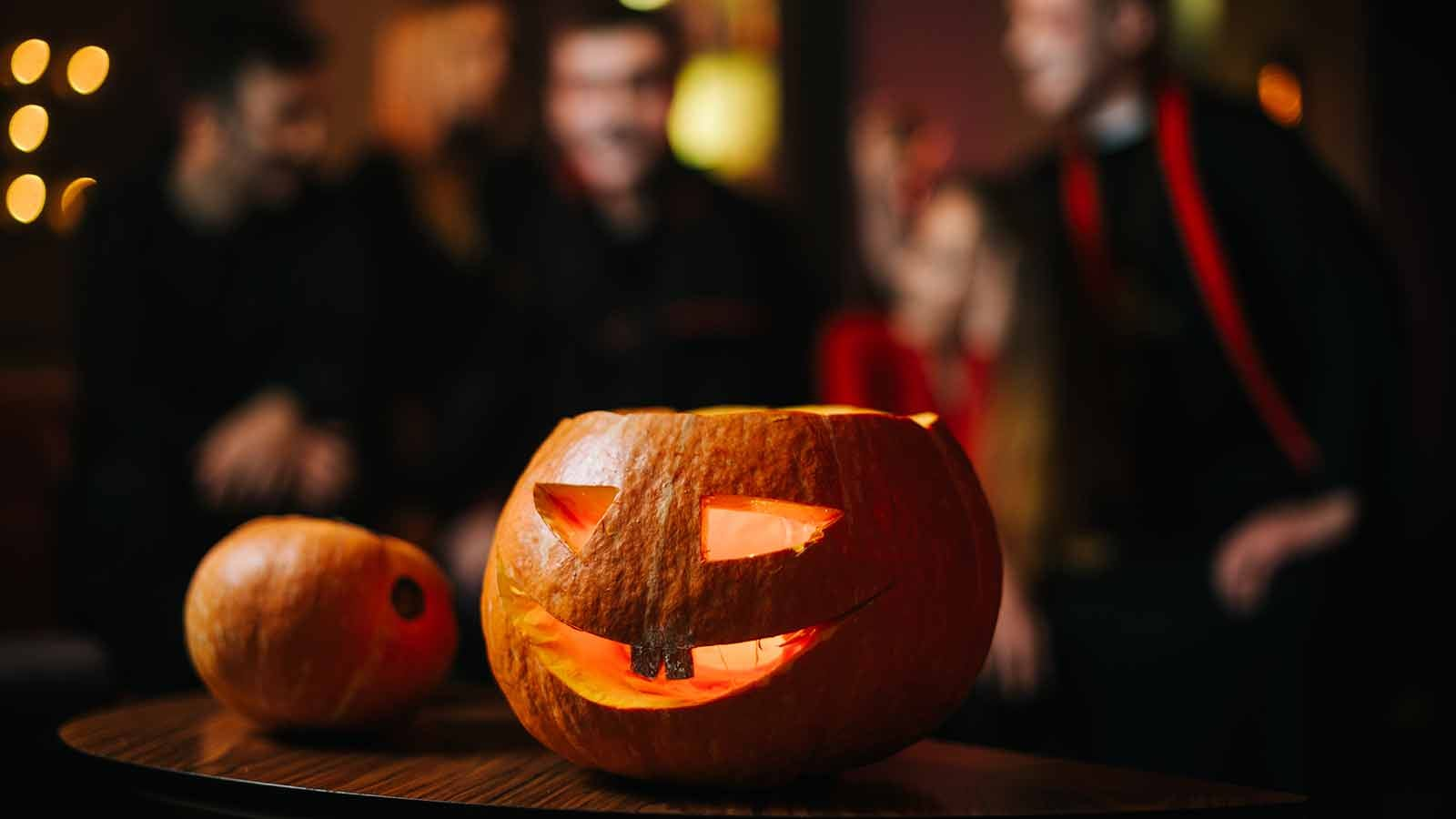 A glowing jack o' lantern sitting on a table with some Halloween party guests in the background.