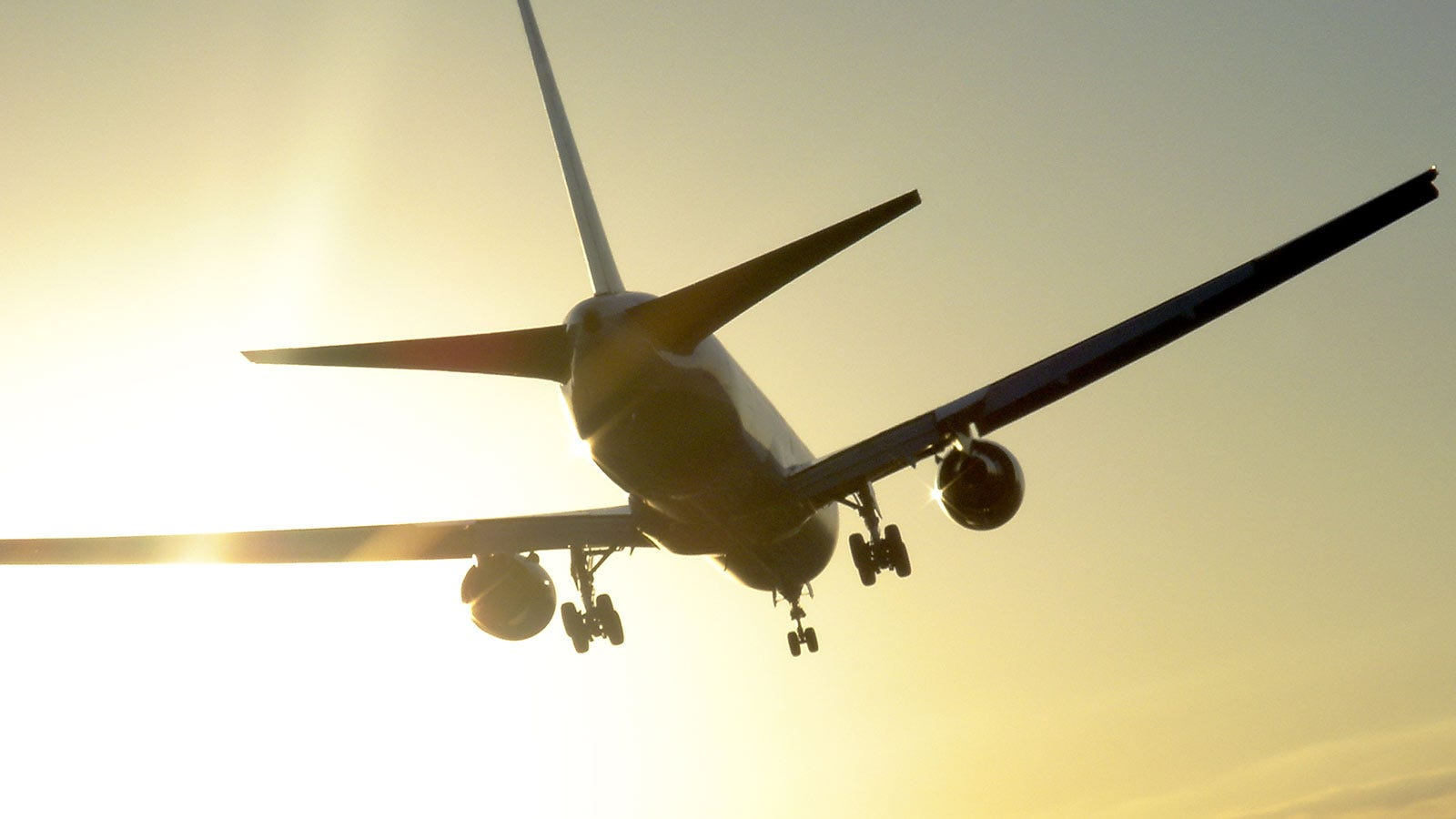 a large passenger aircraft flying off into the sunset