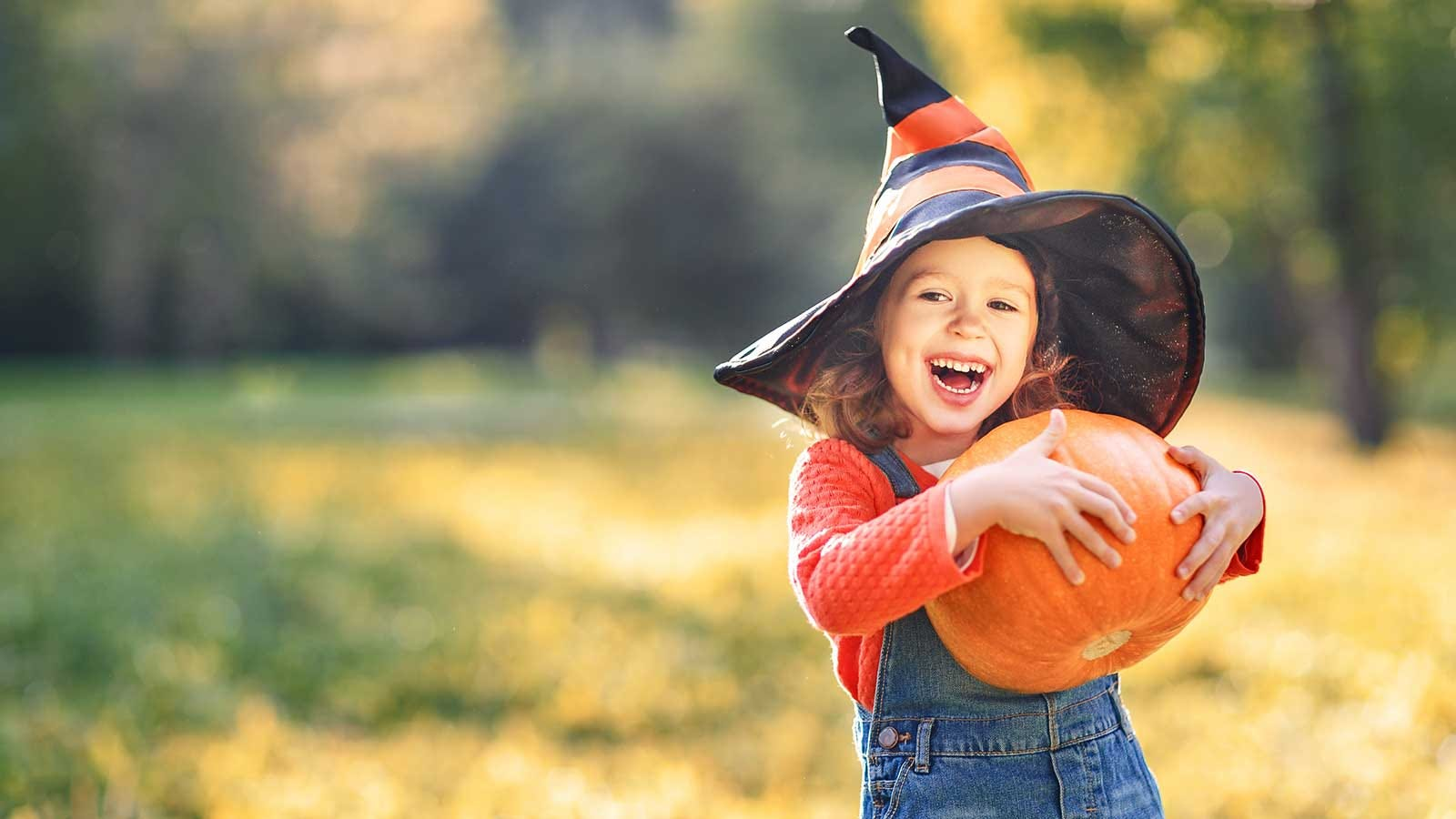 A little girl wearing a witch's hat and carrying a pumpkin.