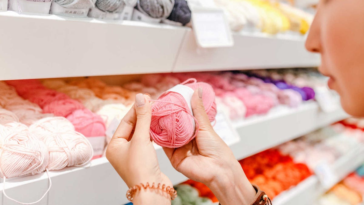 woman selecting yarn in a craft store
