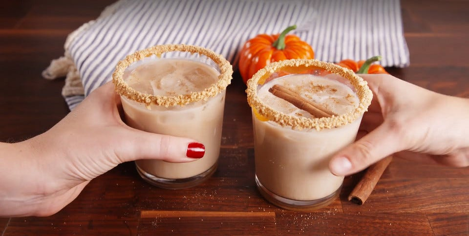 A woman's hand and a man's hand each holding a tumbler full of Pumpkin Spiced White Russian cocktails.