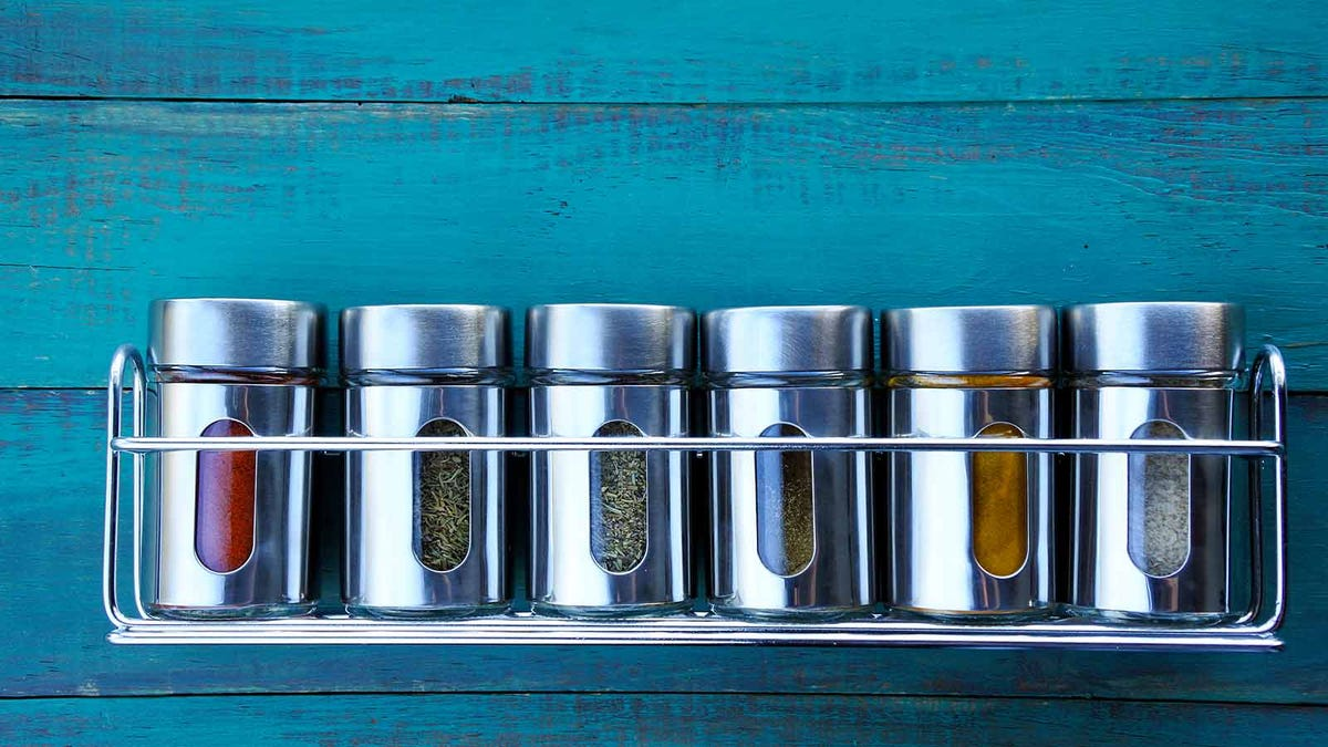 a metal spice rack and spice jars on a weathered turquoise wall