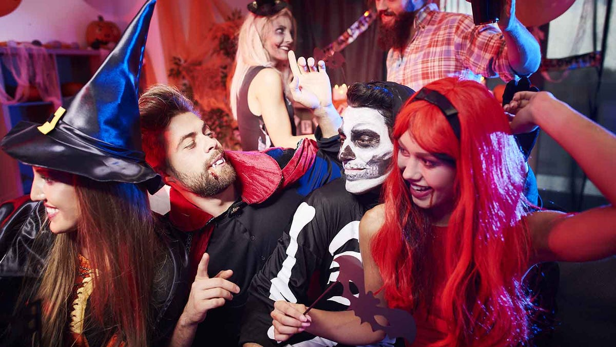 a bunch of people dressed in Halloween costumes dancing at a party