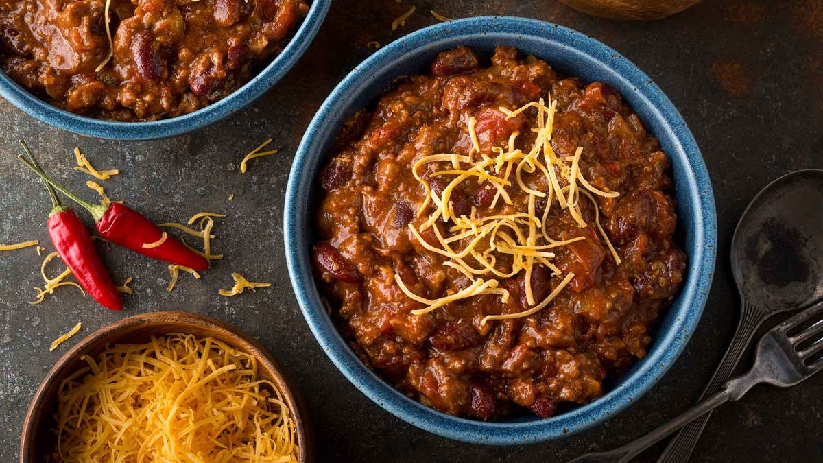 Bowls of chili surrounded by peppers and shredded cheese, resting on a table.