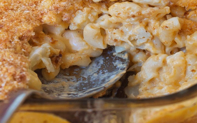 A spoon sticking in a casserole dish full of mac and cheese.