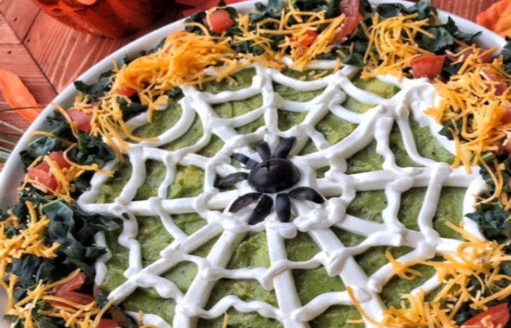 A taco dip that uses sour cream and other ingredients to create a spiderweb.