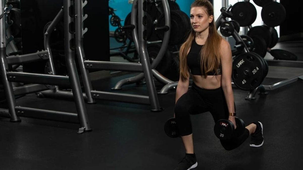 A woman doing dumbbell lunges in a gym.