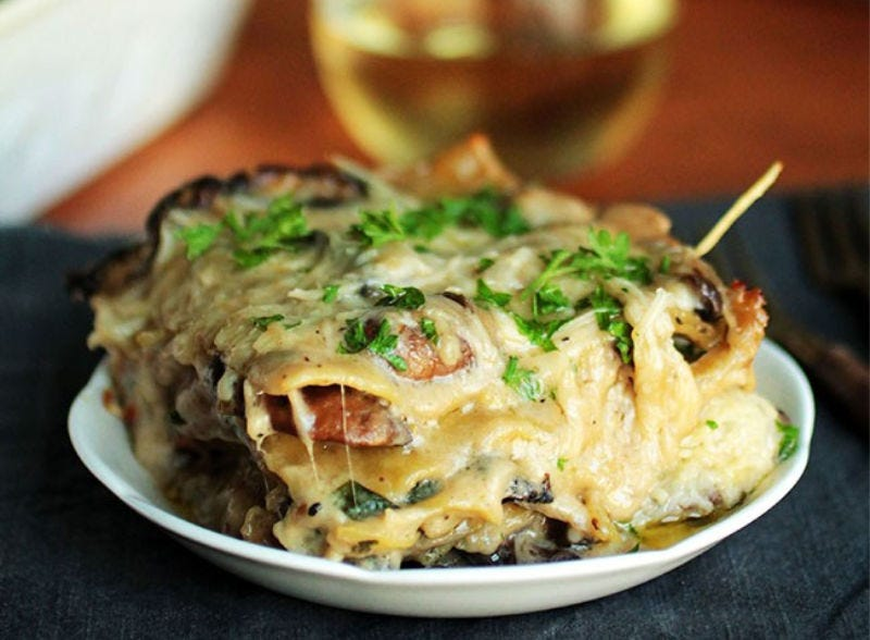 A serving of mushroom and spinach lasagna with a glass of white wine in the background..