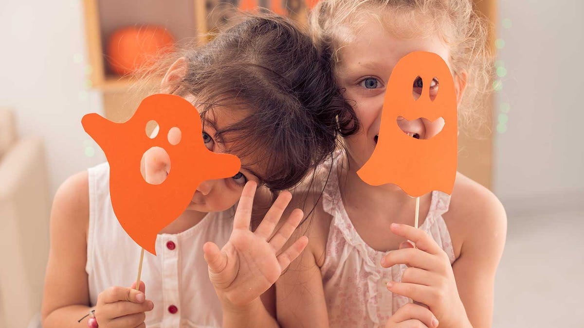 Two little girls hiding behind paper ghost masks.