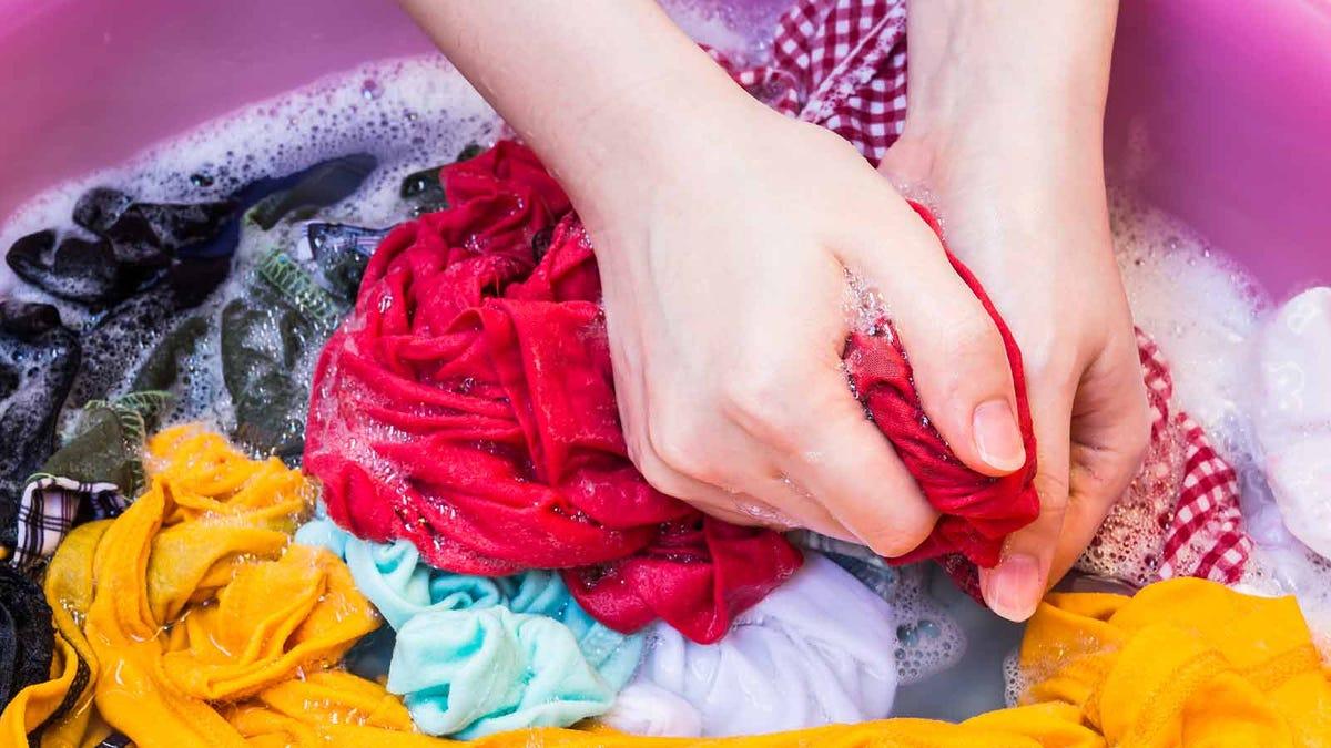 woman hand washing clothing in a wash tub