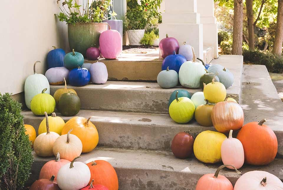 several pumpkins painted in bright colors and arranged on house steps