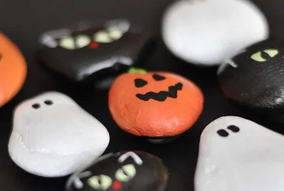 Halloween themed rock magnets, painted like pumpkins, ghosts, and cats