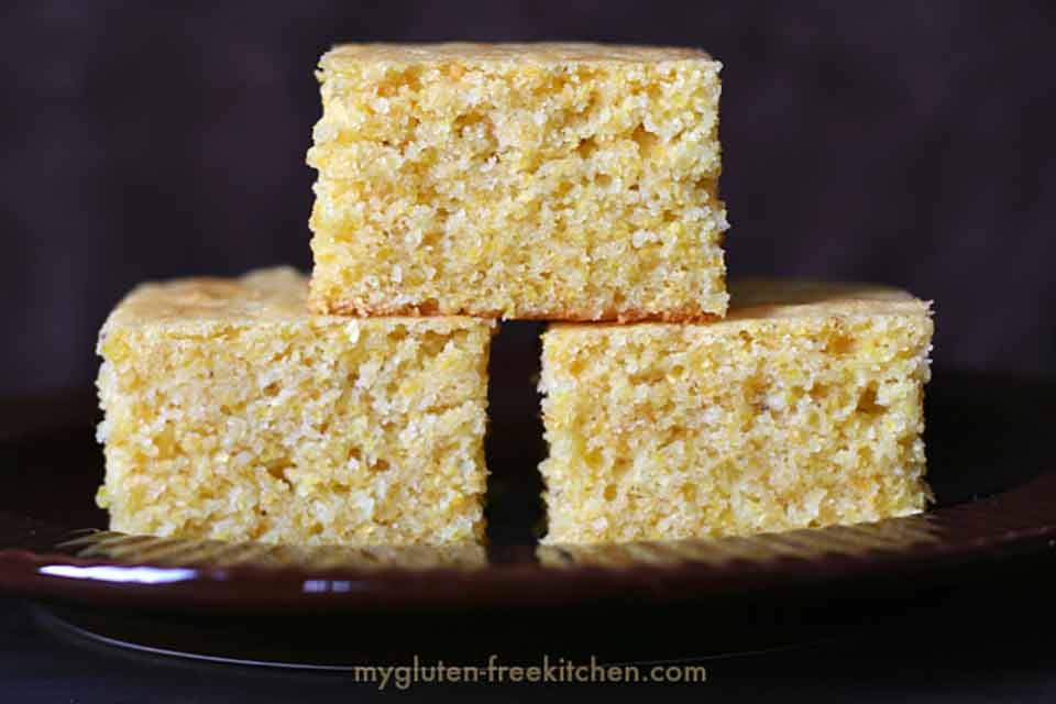 gluten-free cornbread stacked on a dark serving plate