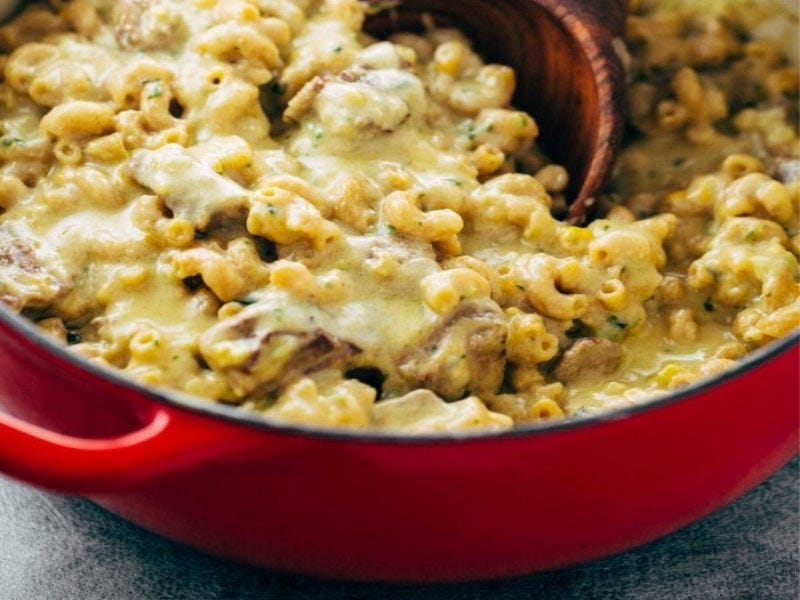 A red skillet filled with steak and cheddar mac and cheese, with a wooden spoon diving in.