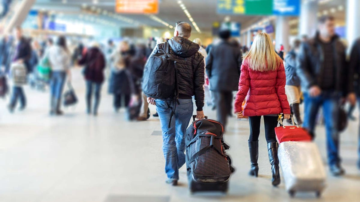 two travelers walking in a busy airport terminal