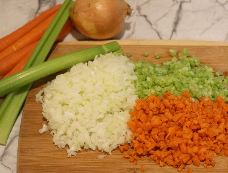 Diced onion, celery and carrot with the whole vegetables in the background.