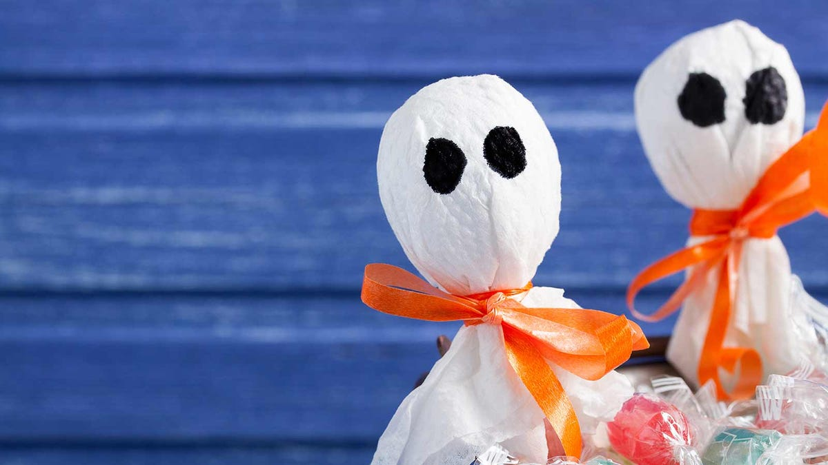 Halloween lollipop ghosts and candies on purple wooden background
