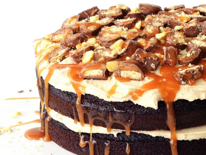 A layered chocolate cake with caramel frosting and chopped twix bar.