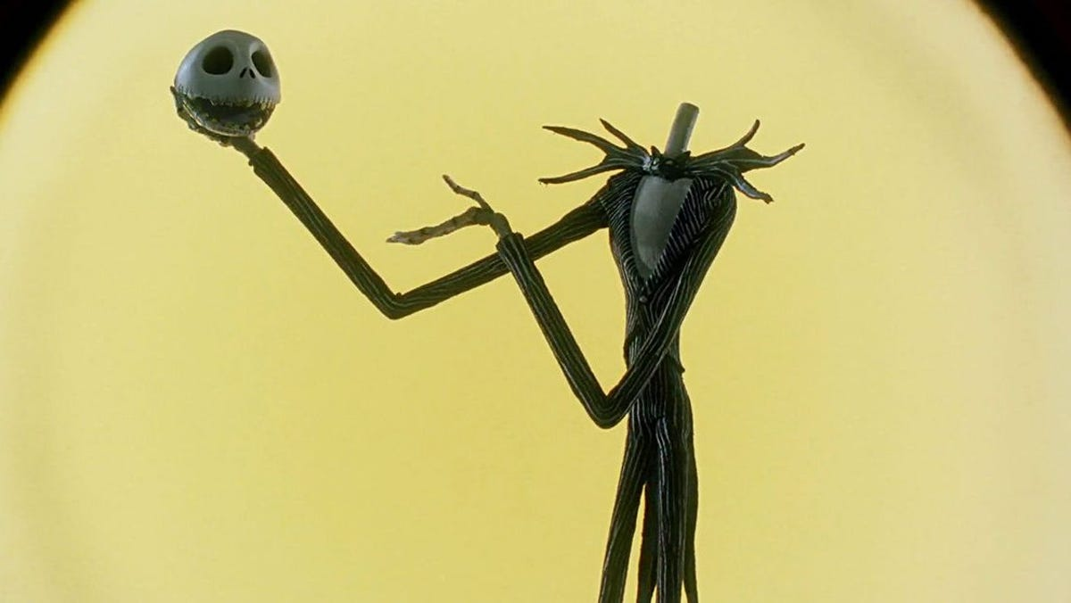 Jack Skellington holding up his head in front of the moon.