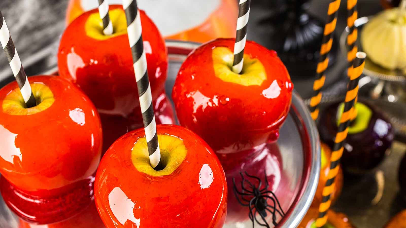 shiny red candy apples with black and white striped sticks resting on a silver platter