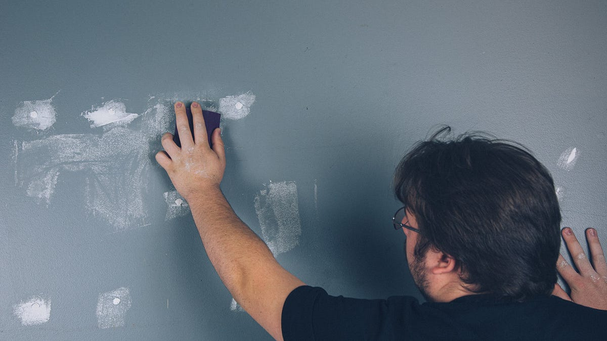 Man sanding spackle to prepare for painting.