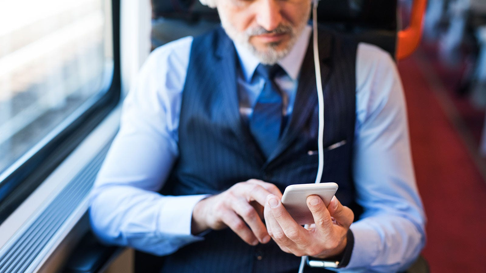 A man on a train listening to something on his phone in one earbud.