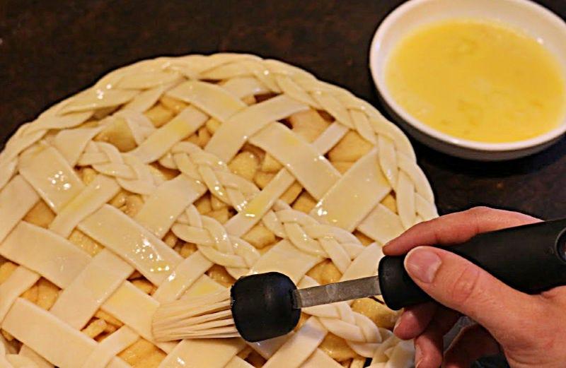 Brushing an egg wash onto a prepared pie crust.