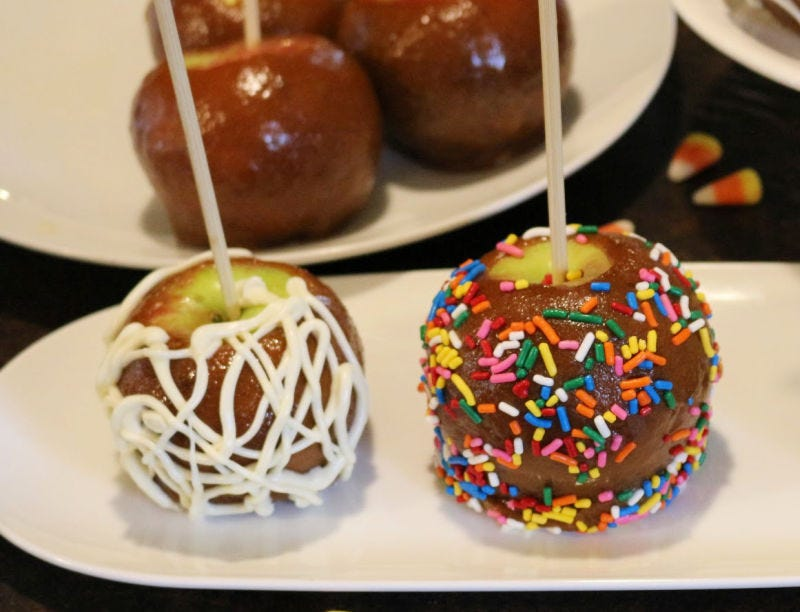 Two caramel apples -- one with drizzled white chocolate on top and the other covered in colorful sprinkles.
