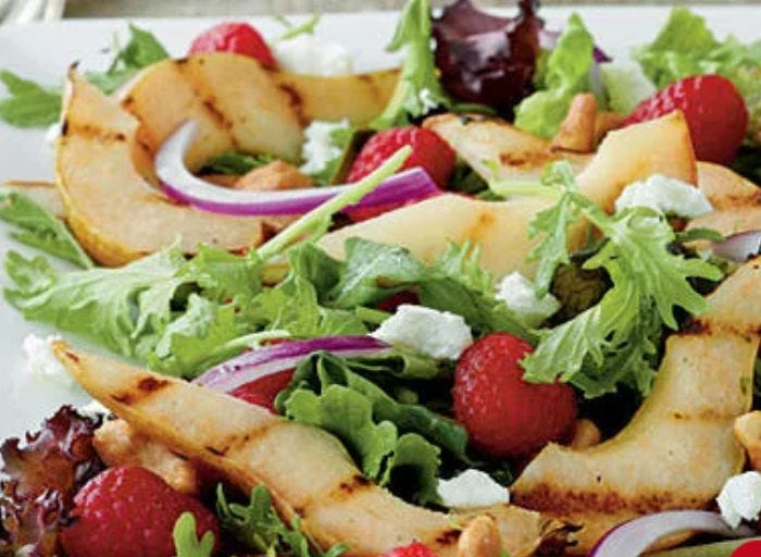 A grilled pear salad with red onion, raspberries and cheese.