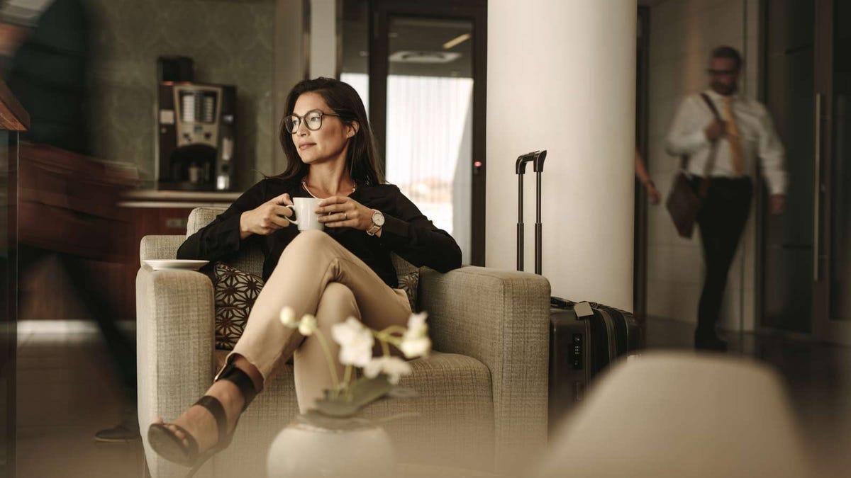 A woman drinking a mug of coffee in a hotel lobby.