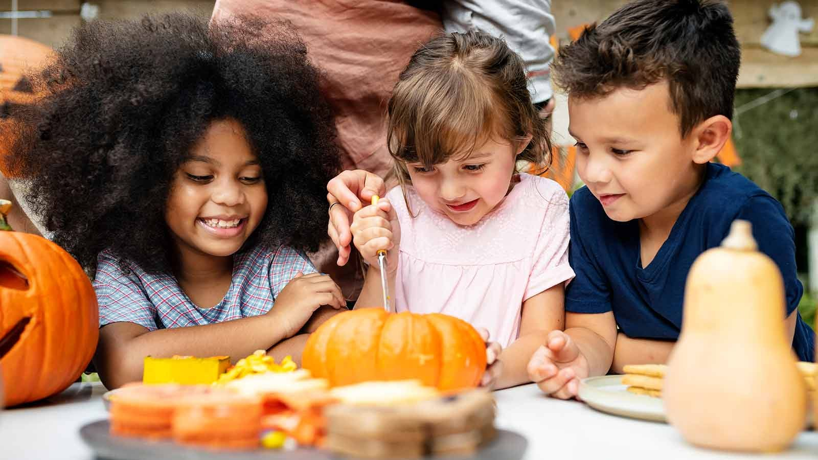 Three children at a table carving a pumpkin.