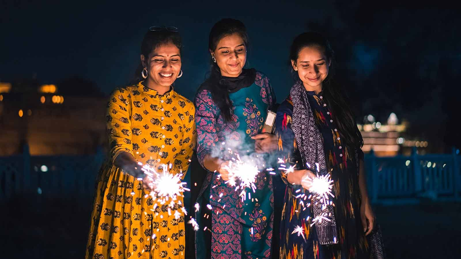 Indian women holding sparklers as they celebrate Diwali