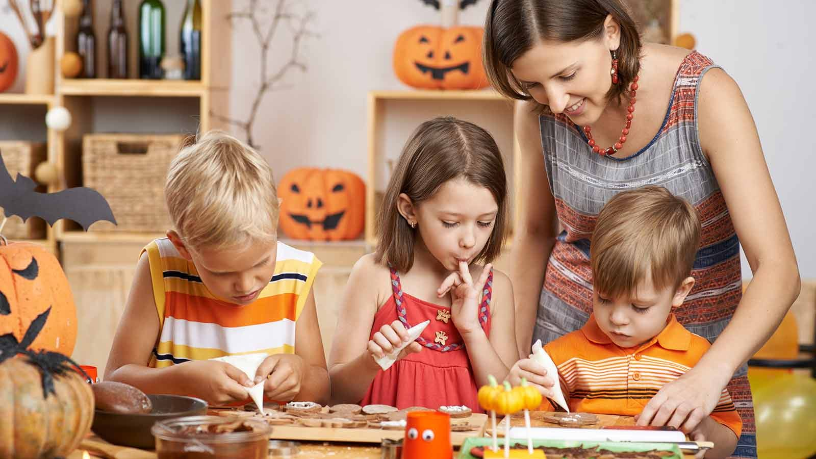 a woman helps young kids make fun Halloween treats