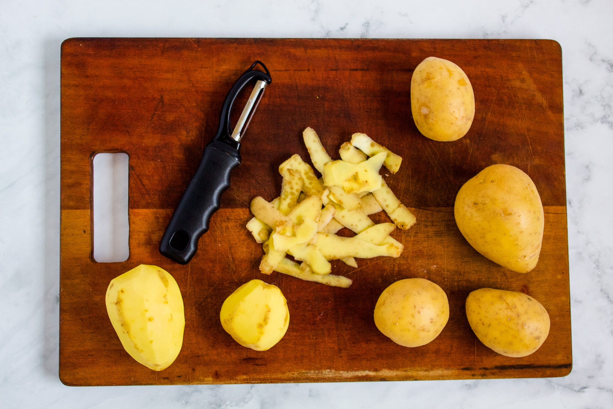 Peeled and sliced Yukon Gold potatoes on a cutting board.